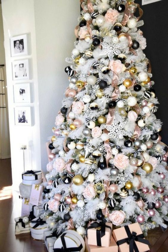 a white Christmas tree with striped, gold, polka dot and pink and silver ornaments plus blooms looks really glam-like