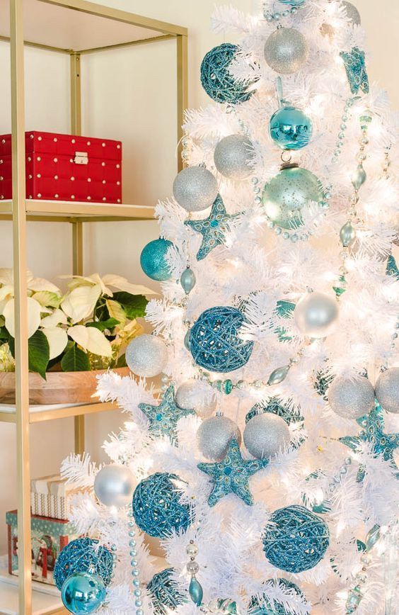 a white Christmas tree with turquoise ornaments, stars, pearly and silver ornaments and beads for a beachy holiday