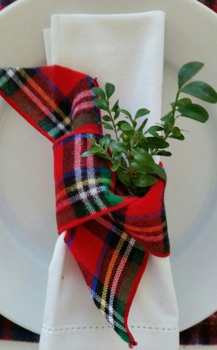 a white napkin with a bright plaid ribbon and some greenery will make your Christmas tablescape very chic and holiday-like