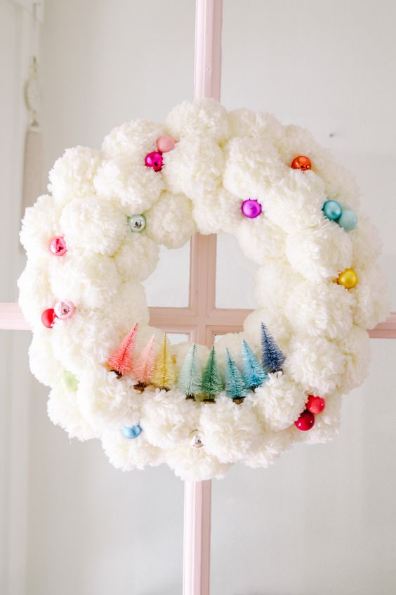 a white pompom Christmas wreath with bright and shiny ornaments and little tinsel trees of all the colors of rainbow