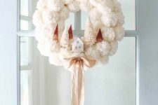 a white pompom Christmas wreath with tinsel trees and a small house plus a silk ribbon bow is very exquisite and cozy