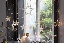 a window styled with star lights and dolls looks very beautiful, modern and Christmassy, it's very cool
