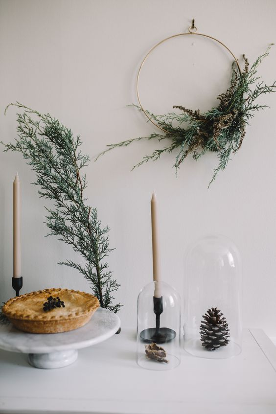 a wreath with dried branches and greenery, neutral candles, a grene branch and a pinecone in a cloche for a Nordic feel
