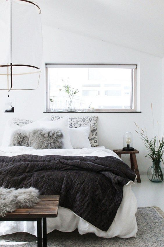 an airy Scandinavian bedroom done in white, with dark stained furniture, neutral bedding, a paper lamp and some plants
