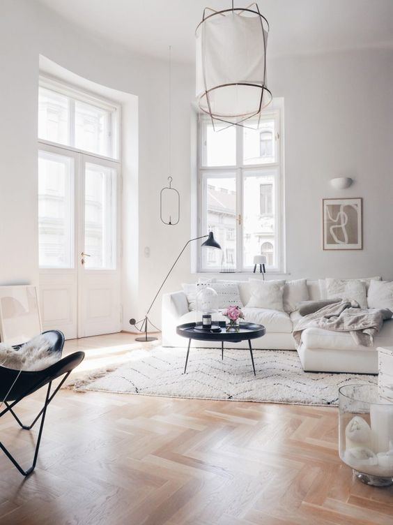 an airy Scandinavian living room with a creamy sectional, a black table and butterfly chair, a paper lamp and a black floor lamp