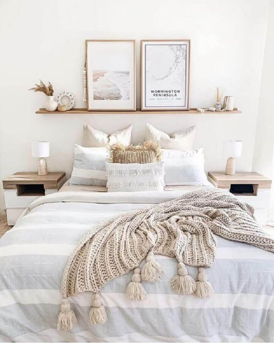 an airy and neutral bedroom with sleek wooden furniture, an open shelf with art and candles and coastal bedding