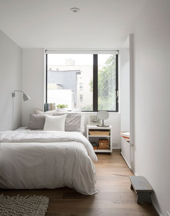 an airy and welcoming small bedroom in white, with white furniture, a tiny bench, a nightstand and a daybed by the window