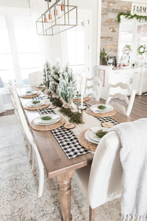 an airy farmhouse Christmas table with a burlap runner, woven chargers, wood slices with monograms, flocked mini trees and candkes