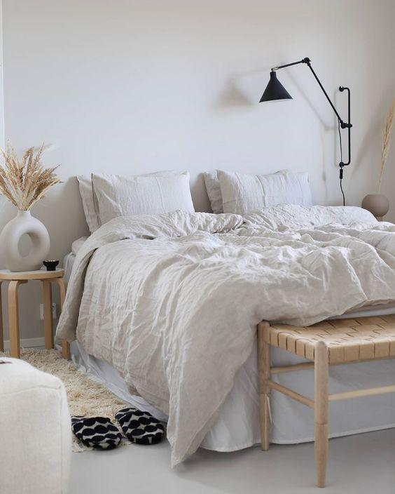 an airy neutral Scandi bedroom with modern furniture, a woven bench, neutral bedding, a fluffy rug, black sconces and grasses