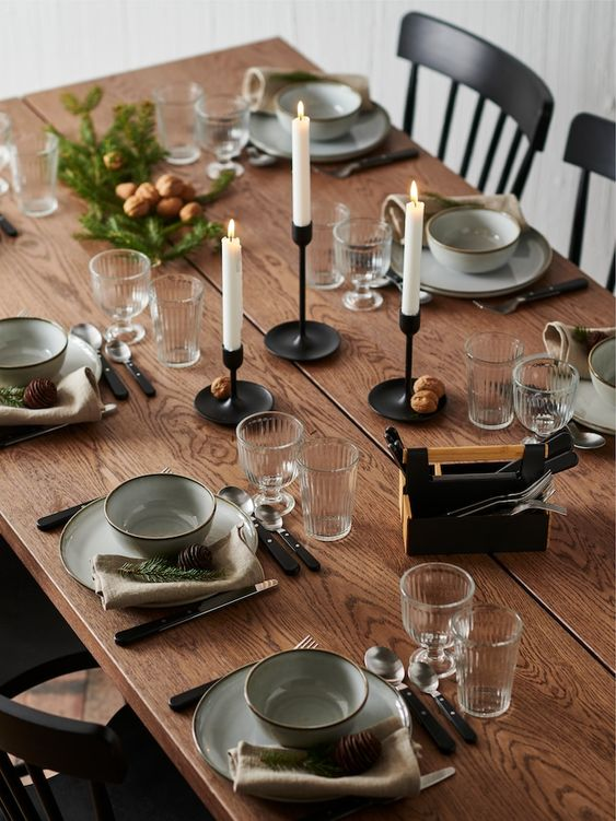 an all-natural Christmas tablescape with candles, grey porcelain, pinecones, fir twigs and simple modern cutlery