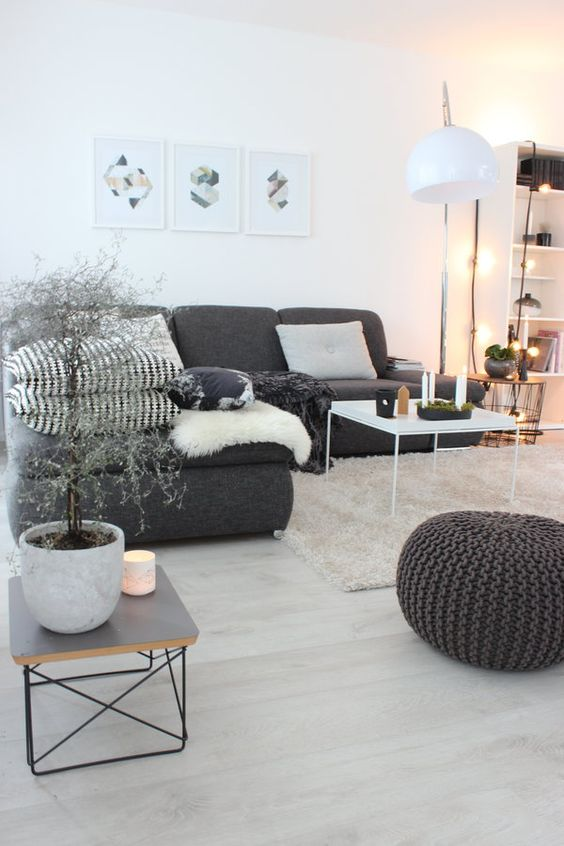 an amazing Scandinavian living room with a graphite grey sofa, monochromatic pillows, a black ottoman, a white table and lamp plus lights and plants