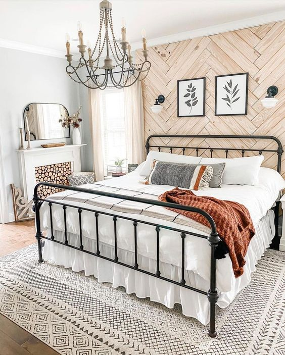 an eclectic bedroom with a wood clad wall, a metal bed, a vintage chandelier, a fireplace with a firewood screen, pretty bedding and a printed rug