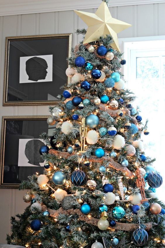 an elegant Christmas tree with navy, blue and green and white ornaments, ribbons, lights and a star topper