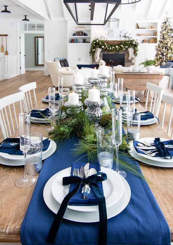 an elegant navy and silver Christmas tablescape with navy linens, fir branches and vintage candlehodlers with cndles