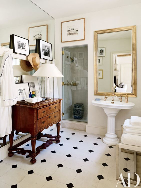 an elegant vintage bathroom with black and white tiles, a heavy wooden cabinet, a mirror in a gold frame, some artworks