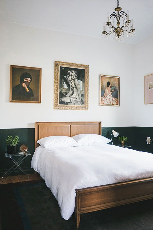 an elegant vintage bedroom with a wooden bed, acrylic nightstands, a gallery wall and a vintage chandelier plus lamps