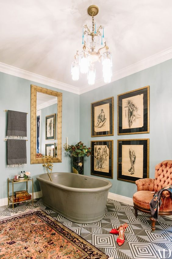 an elegant vintage-inspired bathroom with blue walls, a grey tub, a gallery wall, a mirror in a gold frame, a boho rug and a vintage chandelier