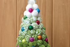 an ombre white to green pompom Christmas tree with colorful ornaments and a pretty silver glitter topper is a cool idea