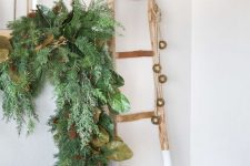 beautiful Christmas decor with a lush fir garland with leaves and pinecones, a color block ladder with bells is amazing