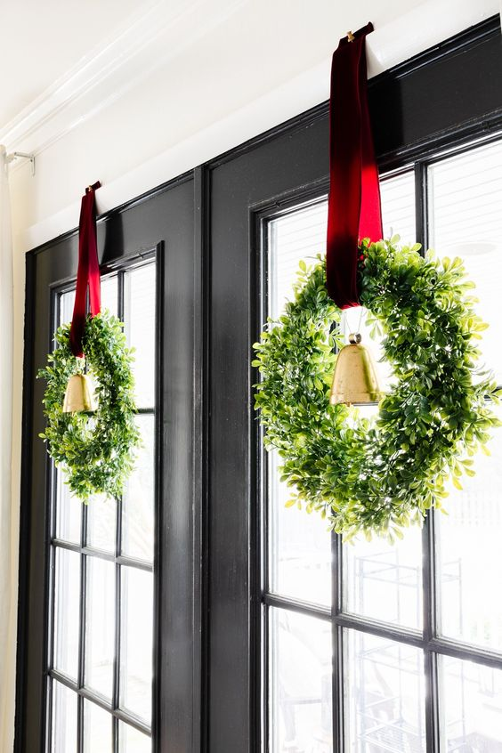 beautiful rustic Christmas wreaths of boxwood with large vintage bells and burgundy ribbons are lovely window or front door decorations
