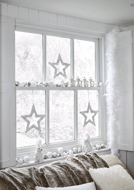 beautiful white and silver Christmas window decor with ornaments, candle lanterns, twine stats and squirrels is magical