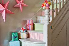 bright Christmas staircase decor with bold wallpaper, brightly wrapped gift boxes, bold stars and paper garlands on the wall
