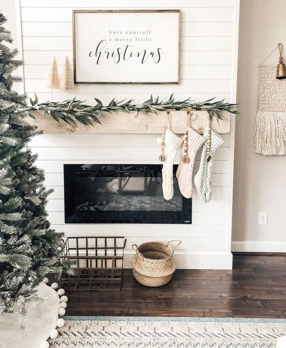 chic Scandinavian mantel decor with greenery, wooden beads, neutral stockings and neutral tinsel Christmas trees