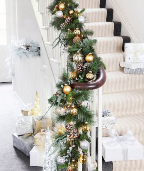 Festive banister garland with fake foliage and pine cones, gold baubles, silver and gold wrapped Christmas presents W&H 12/2010 pub orig