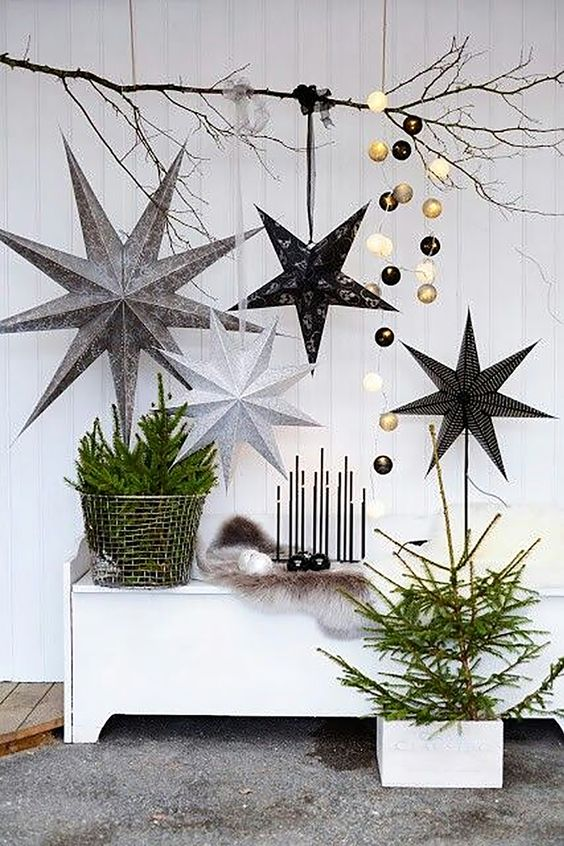 classy Scandinavian Christmas decor with oversized cardboard stars, black and gold lights, faux fir, a small tree and branches