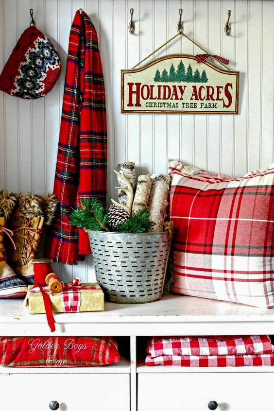 decorate your entryway with a plaid scarf, plaid pillows, blankets and gift boxes, add branches and pinecones to give the space a holiday feel at once