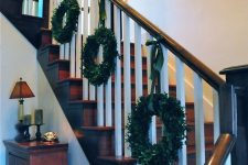 greenery christmas wreaths used to decorate a staircase