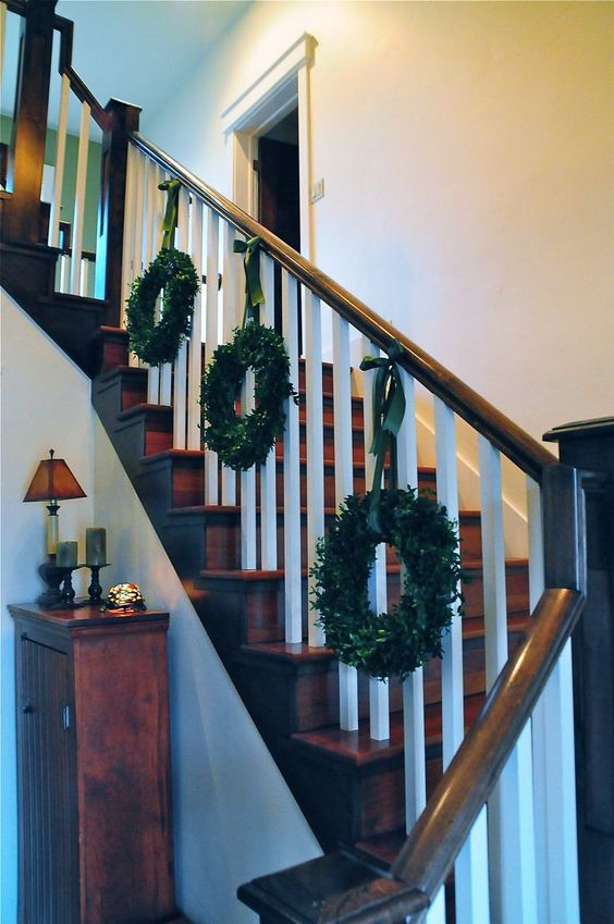 decorating the railing with pretty Christmas wreaths on ribbons is an easy way to bring a touch of Christmas to your space