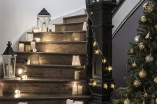 elegant Christmas staircase decor with candle lanterns, mini lanterns of paper, star garlands and an oversized star on the wall