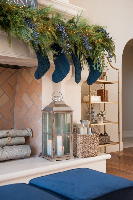 elegant blue Christmas decor with a fir garland with lights, berries, navy stockings and navy cushions at the fireplace