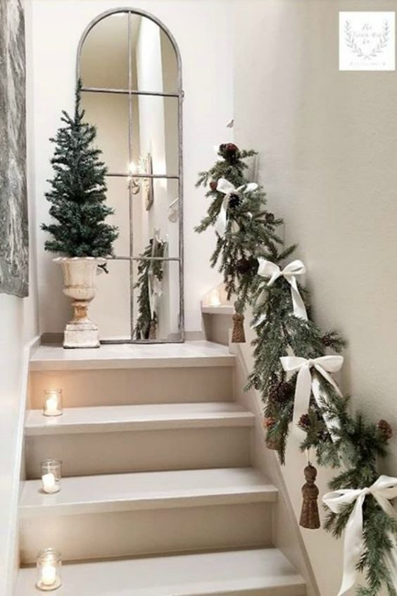 elegant railing decor with fir branches, white bows and large tassels plus candles in jars lining up the staircase
