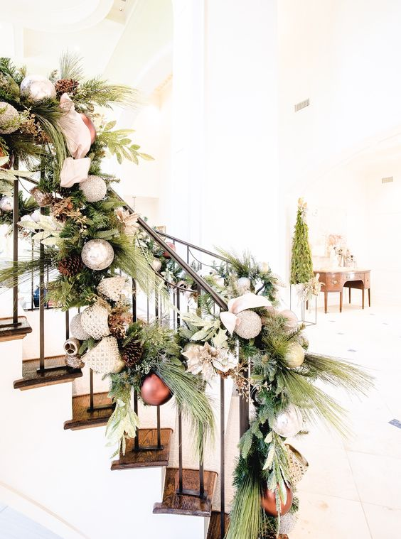 elegant vintage railing decor with fir branches, foliage, neutral and metallic ornaments, ribbons and bows is ideal for winter