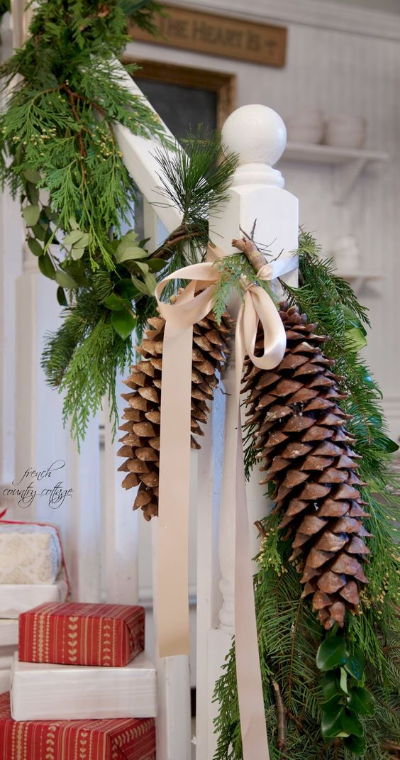 fresh foliage, evergreens, oversized pinecones and neutral bows are amazing to decorate your railing in farmhouse style for Christmas
