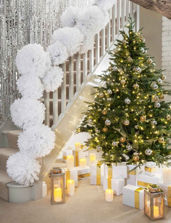 glam Christmas staircase decor with long silver fringe on the wall and white paper pompoms on the railing is fun and easy