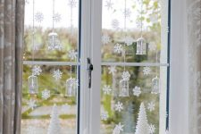 glam Christmas window decor with snowflakes, mini trees, lights, greenery and hanging candle lanterns is a very chic idea