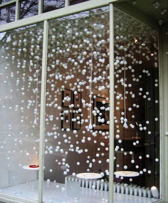 hang pompoms in front of the window to make the space feel snowy and fairy-tale-like, it's a very easy idea