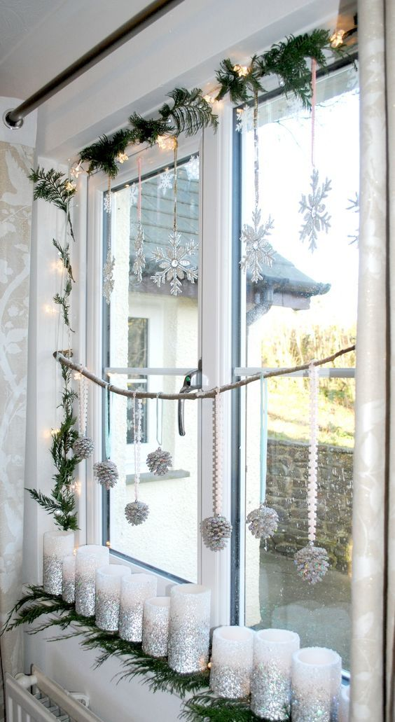 hanging silver snowflakes, a fir garland, lights, silver glitter pinecones on ribbns and silver glitter candles to decorate the window in snowy fairy-tale style