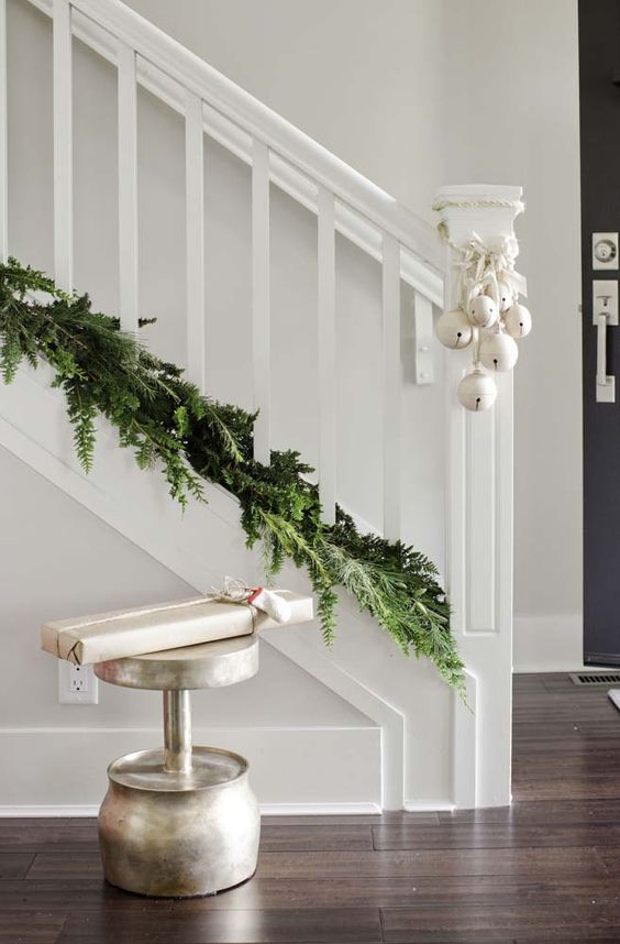 lovely Christmas staircase decor with a lush greenery garland and lots of white bells attached to it is chic and simple