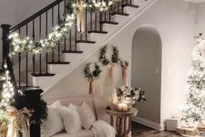 lovely and chic Christmas railing decor with an evergreen garland with lights and tan bows is pure elegance and looks very glam
