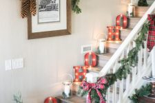 lovely farmhouse Christmas staircase decor with marquee letters, candle lanterns, evergreen garlands and plaid bows, pinecones and a mini tree