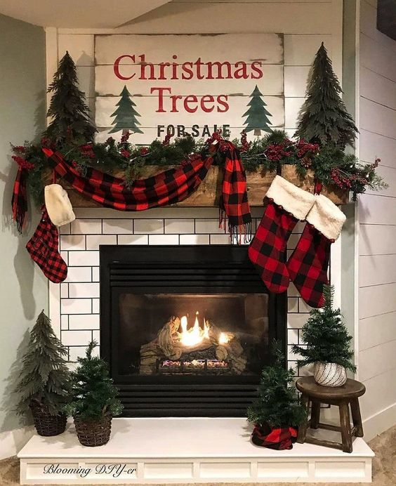 lovely rustic Christmas mantel with a plaid scarf and stockings, mini Christmas trees on the mantel and around the fireplace