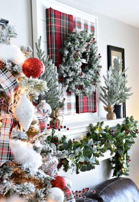 lush Christmas decor with a plaid art and a snowy wreath,, a greenery and berry garland, a flocked Christmas tree with red gltter and silver ornaments
