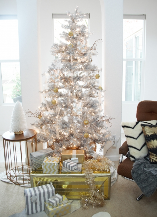 metallic decor ideas - a silver Christmas tree with gold and white ornaments and gift boxes wrapped with gold and silver
