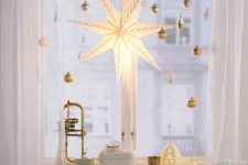 metallic ornaments and a star lantern hanging on the window give a chic and glam look to the space in winter