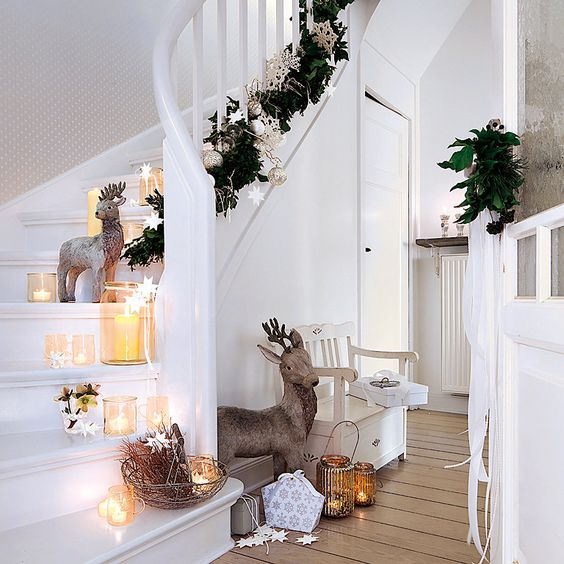 mini glass candle lanterns, deer, stars, a fir garland with ornaments and some vine in a bowl for chic Christmas staircase decor