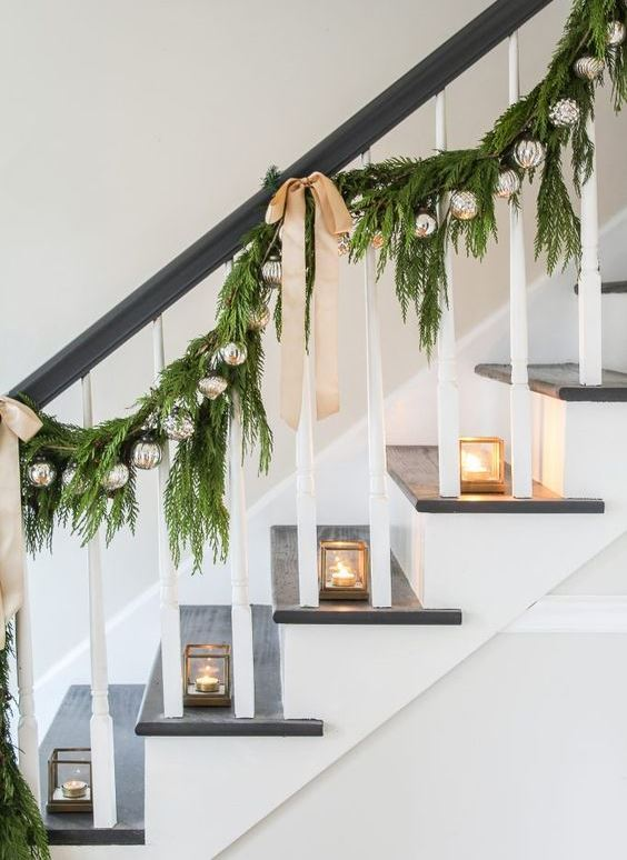 mini glass candleholders, an evergreen garland with silver ornaments and tan bows on the railing for elegant modern Christmas decor